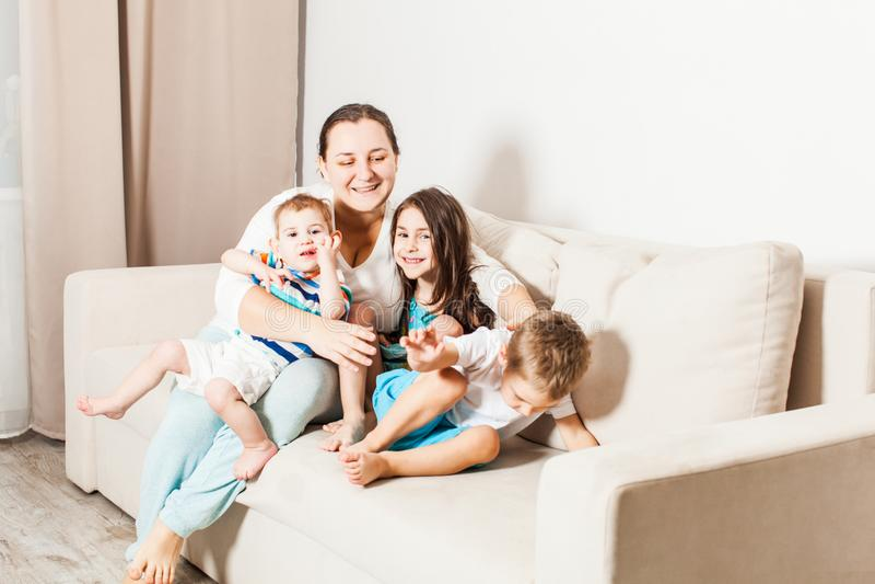 Kvinna med hennes lilla ungar på soffan royaltyfri foto