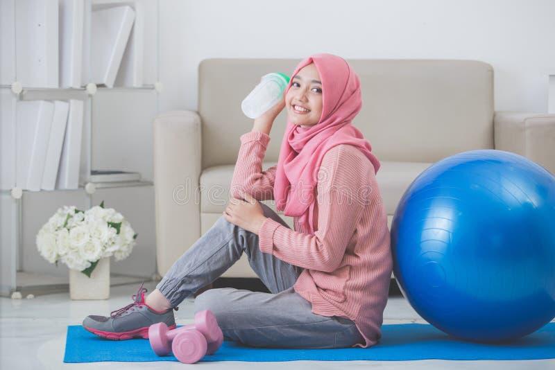 Kvinna med hijab som hemma gör övning royaltyfri foto