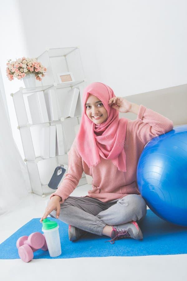 Kvinna med hijab som hemma gör övning arkivfoton