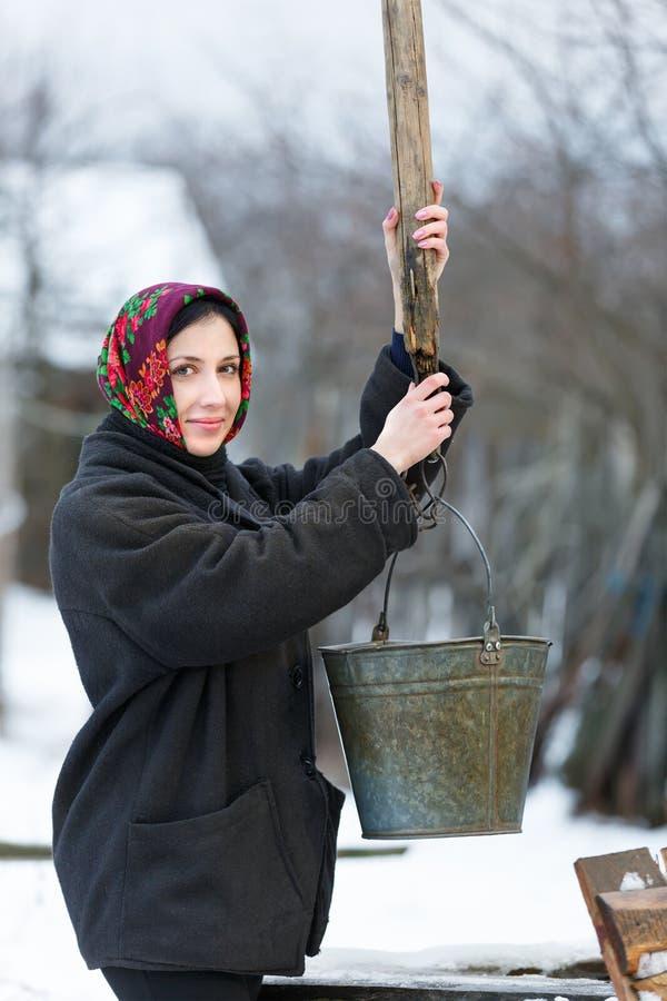 Kvinna med hinken som samlar vatten från brunnen royaltyfria bilder