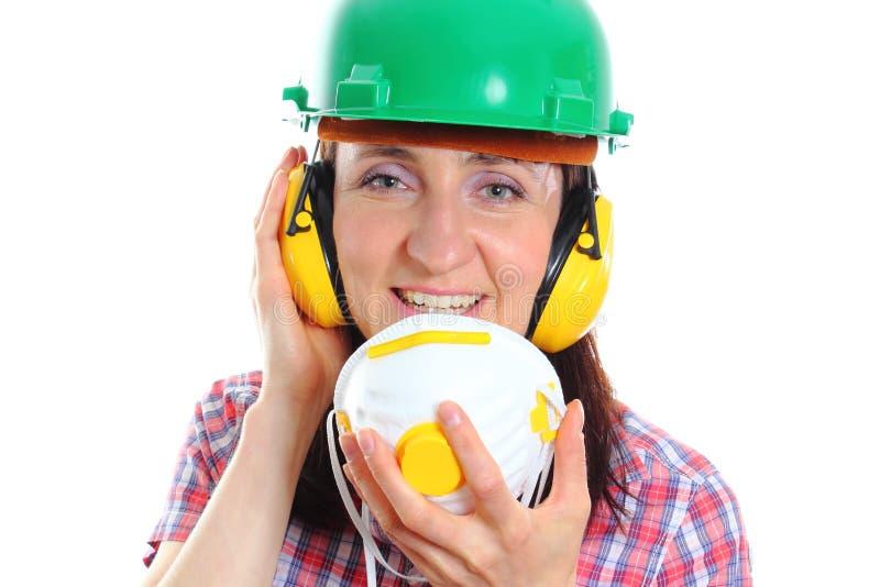 Kvinna med hjälmen och hörlurar för skyddande maskering den bärande arkivbild