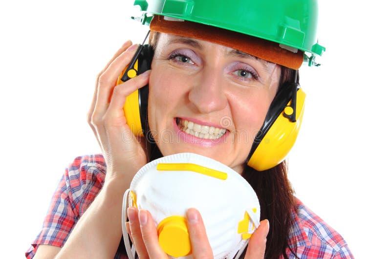 Kvinna med hjälmen och hörlurar för skyddande maskering den bärande arkivfoton