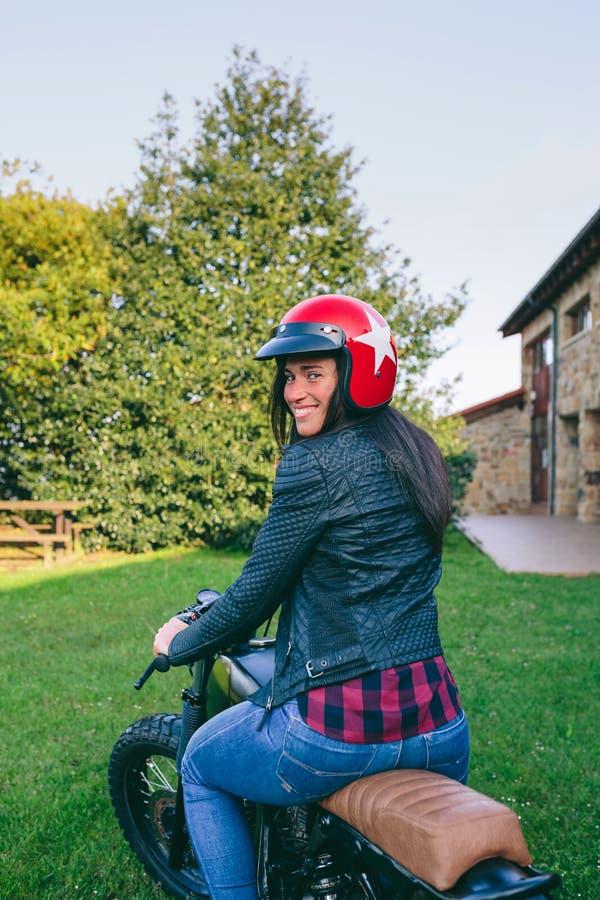 Kvinna med hjälmen som rider den beställnings- mopeden royaltyfri foto