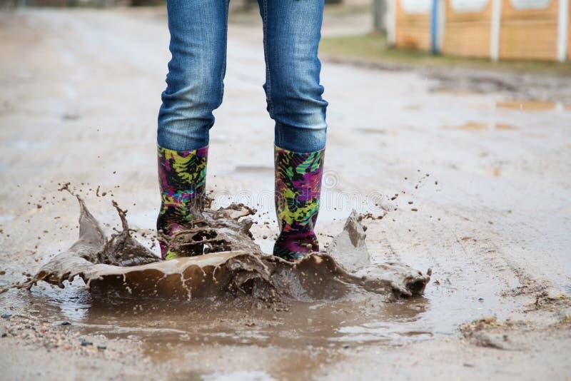 Kvinna med hopp för regnkängor fotografering för bildbyråer
