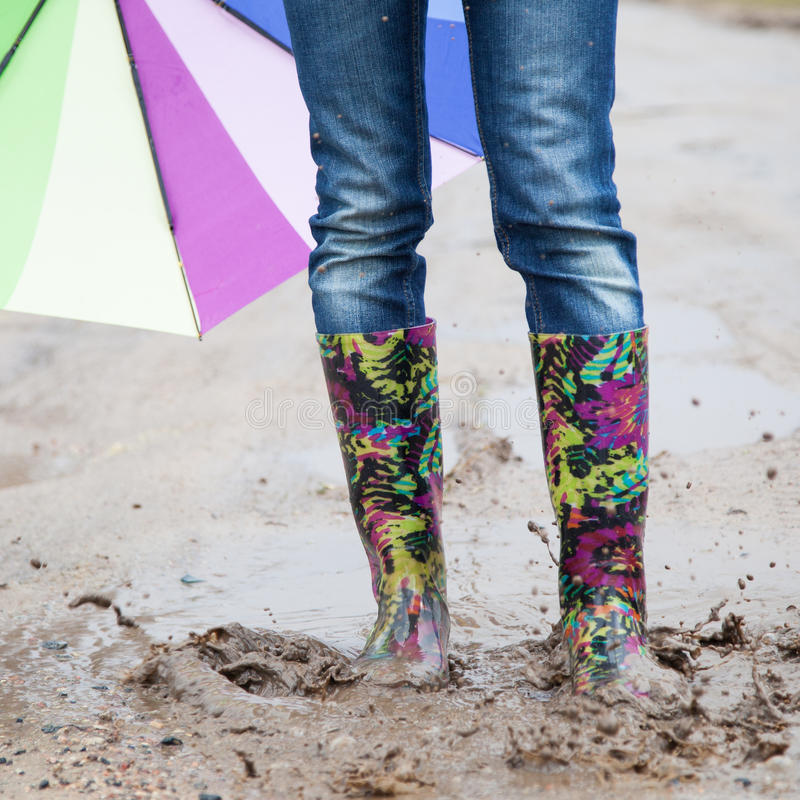 Kvinna med hopp för regnkängor arkivfoto