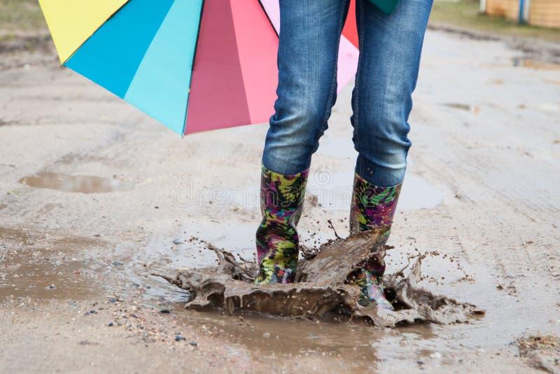 Kvinna med hopp för regnkängor arkivbild