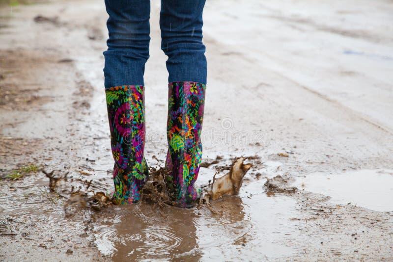 Kvinna med hopp för regnkängor arkivbilder