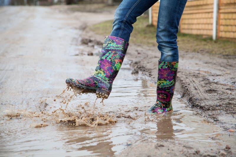 Kvinna med hopp för regnkängor royaltyfri foto