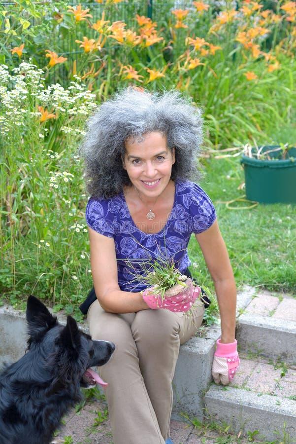 Kvinna med hunden i hennes trädgård royaltyfri bild