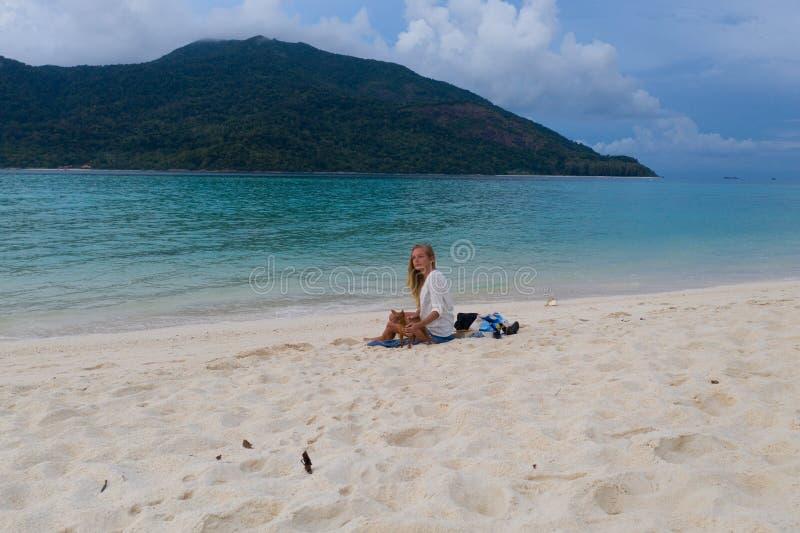 Kvinna med hunden som kopplar av på den sandiga stranden arkivfoton