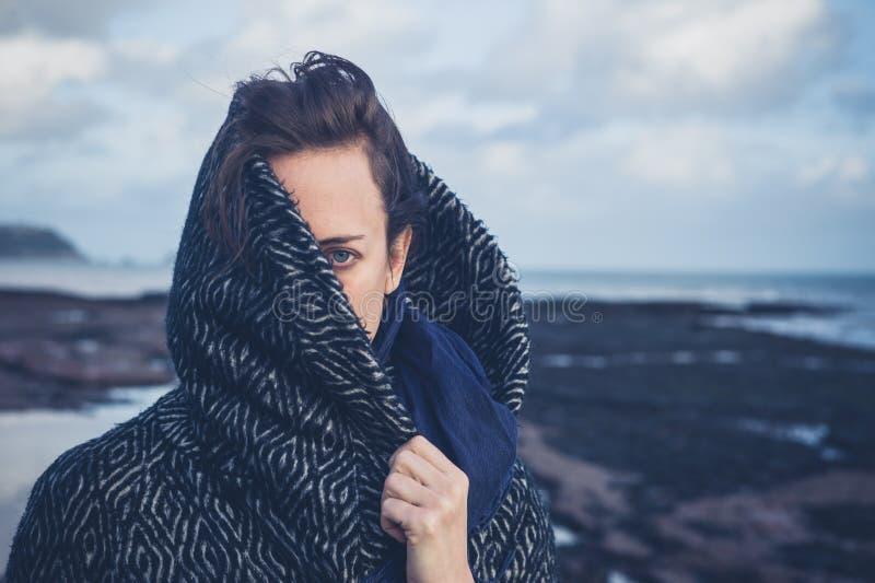 Kvinna med huven på stranden arkivfoton