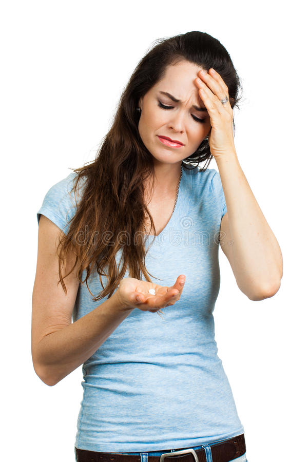 Kvinna med huvudvärken som ser preventivpilleren arkivbild
