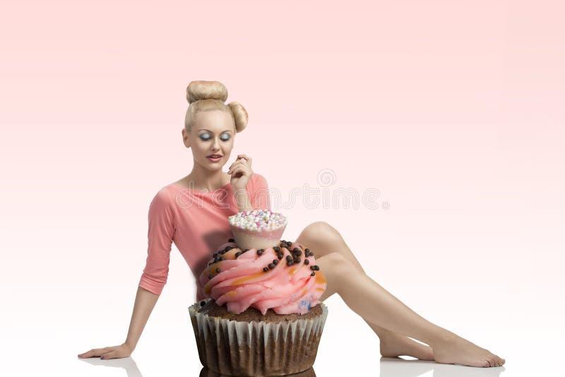 Kvinna med idérik blick och muffin arkivfoto
