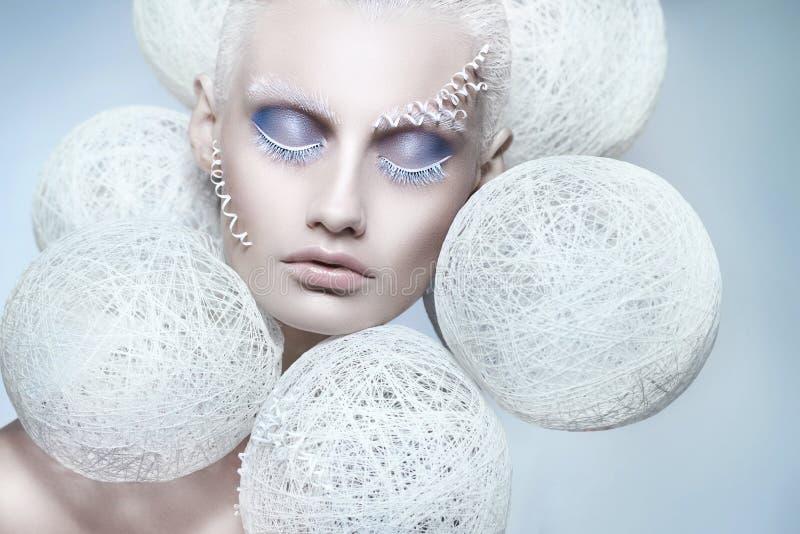 Kvinna med idérik vit och blå makeup Härlig vinterstående fotografering för bildbyråer