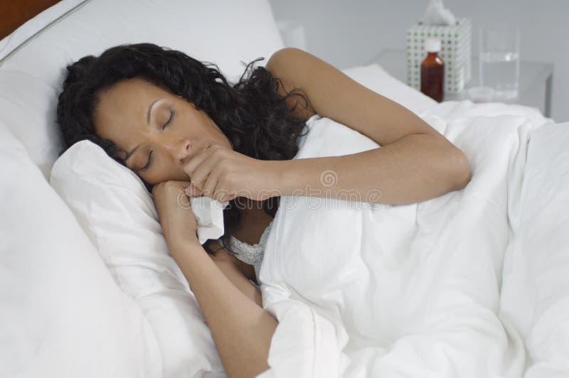 Kvinna med influensa som ligger i säng arkivbilder