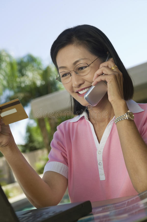 Kvinna med köpet för bärbar datordanandekreditkort på mobiltelefonen arkivbild