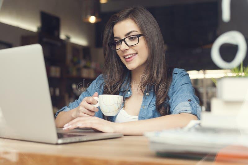Kvinna med kaffe genom att använda bärbara datorn arkivfoto