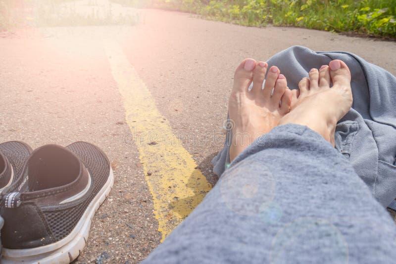 Kvinna med kal fot och ryggsäck som sitter på en asfaltväg med en gul enkel väglinje väntande medel för royaltyfri foto