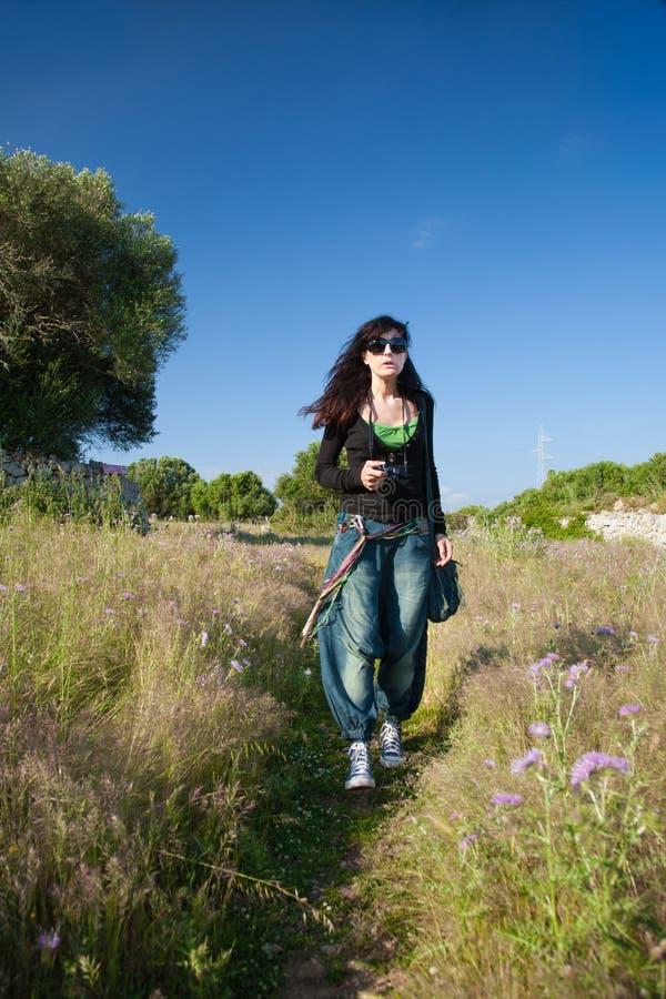 Kvinna med kameran som går på fältet arkivbilder