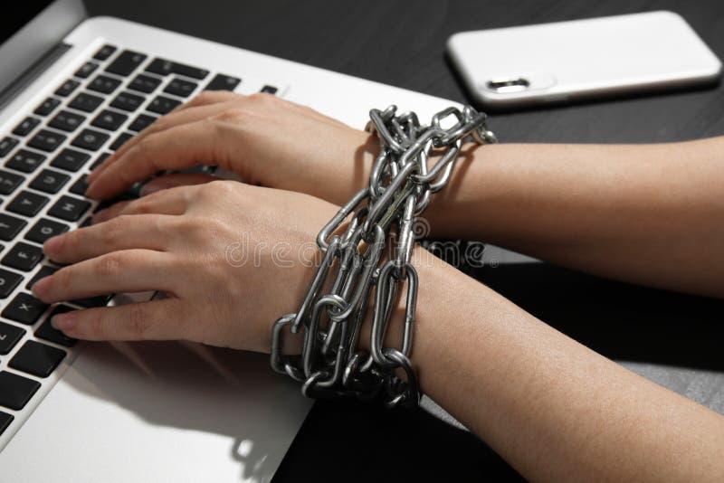 Kvinna med kedjade fast händer genom att använda bärbara datorn på svart bakgrund Enkelt tr?d i dimma arkivfoton
