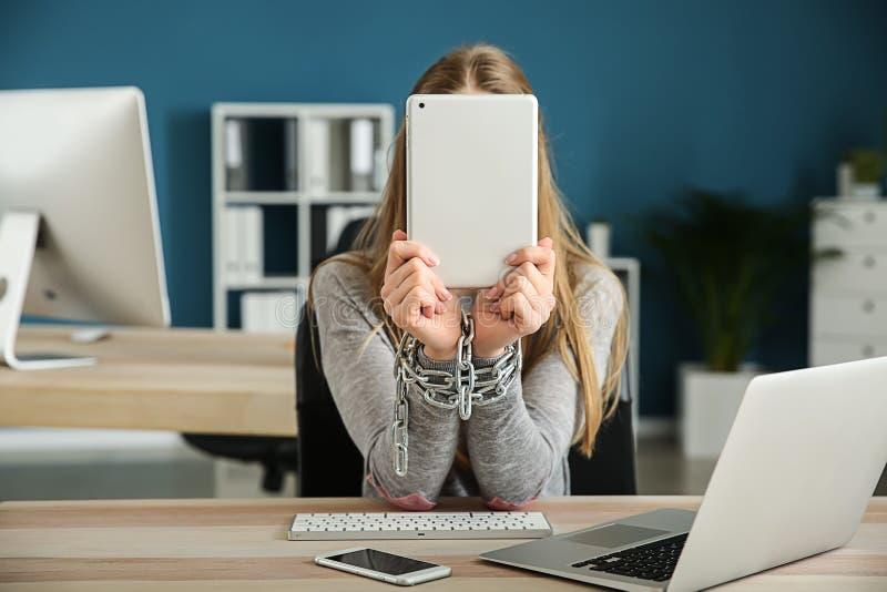 Kvinna med kedjade fast händer och moderna apparater på trätabellen Begrepp av b?jelse royaltyfria foton