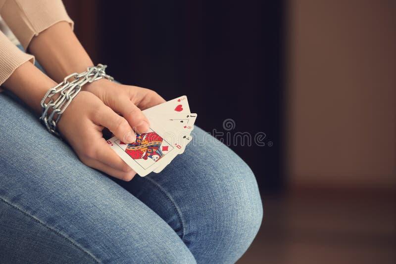 Kvinna med kedjade fast händer som rymmer spela kort, closeup royaltyfri fotografi