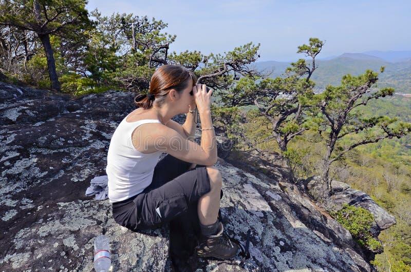 Kvinna med kikare på ett berg royaltyfri foto