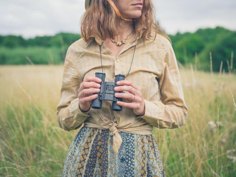 Kvinna med kikare som står i äng royaltyfri fotografi