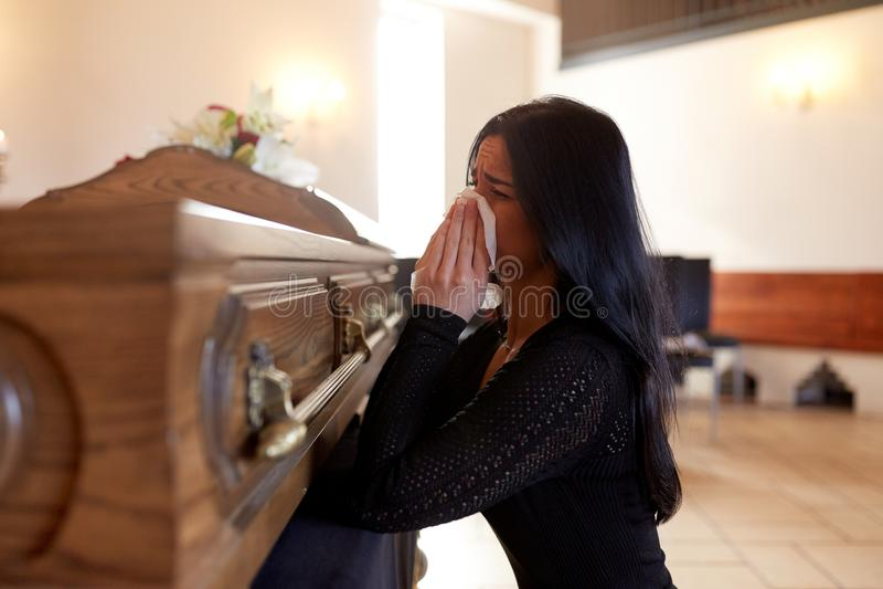 Kvinna med kistagråt på begravningen i kyrka arkivbild
