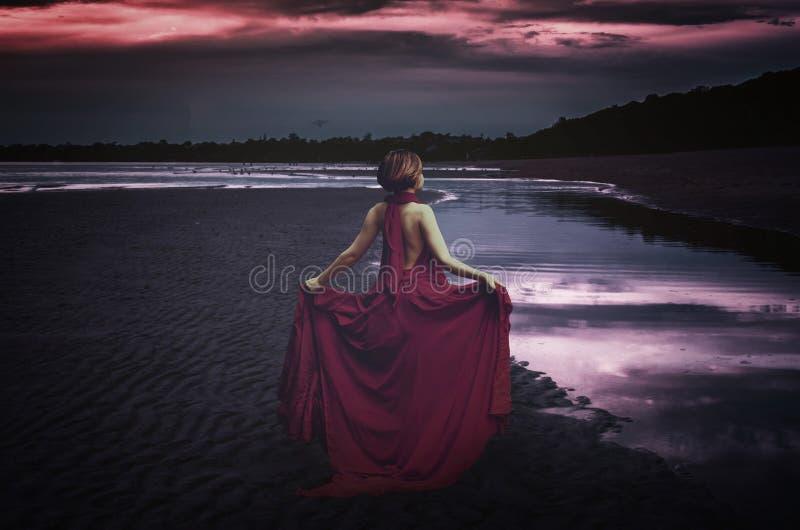 Kvinna med klänningen på havet royaltyfri foto