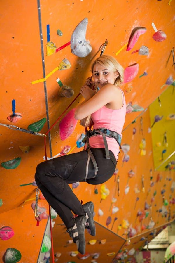 Kvinna med klättringutrustning som hänger på ett rep royaltyfria foton
