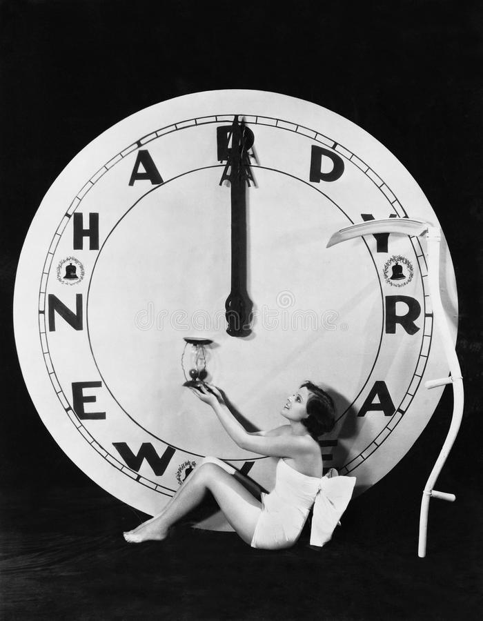 Kvinna med klockan på midnatt på helgdagsafton för nya år (alla visade personer inte är längre uppehälle, och inget gods finns Le arkivfoton