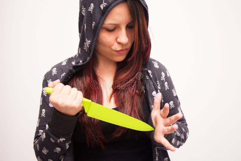 Kvinna med kniven i den vita bakgrunden royaltyfri bild