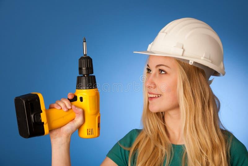 Kvinna med konstruktörhjälmen och den elektriska skiftnyckeln som är lyckliga att göra till royaltyfri fotografi