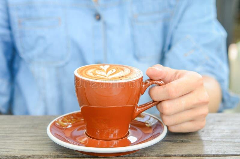 Kvinna med kopp kaffelattekonst på kafét arkivfoton