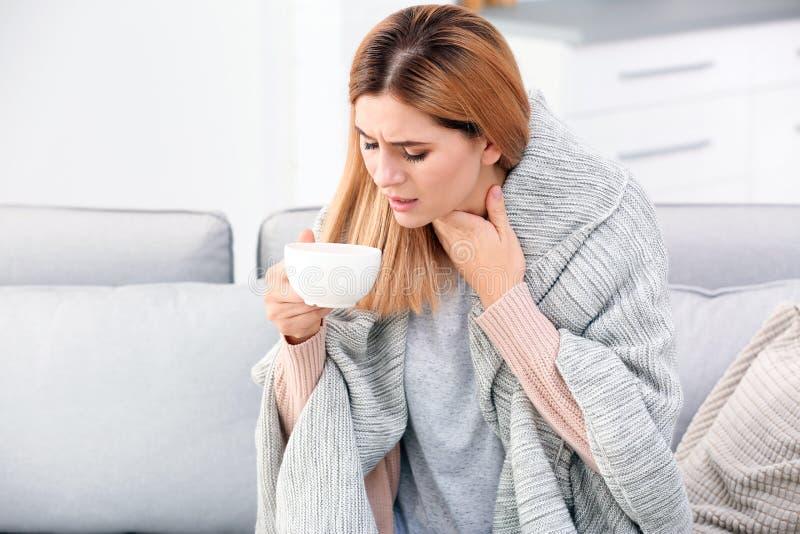 Kvinna med kopp te för hosta på soffan royaltyfri bild