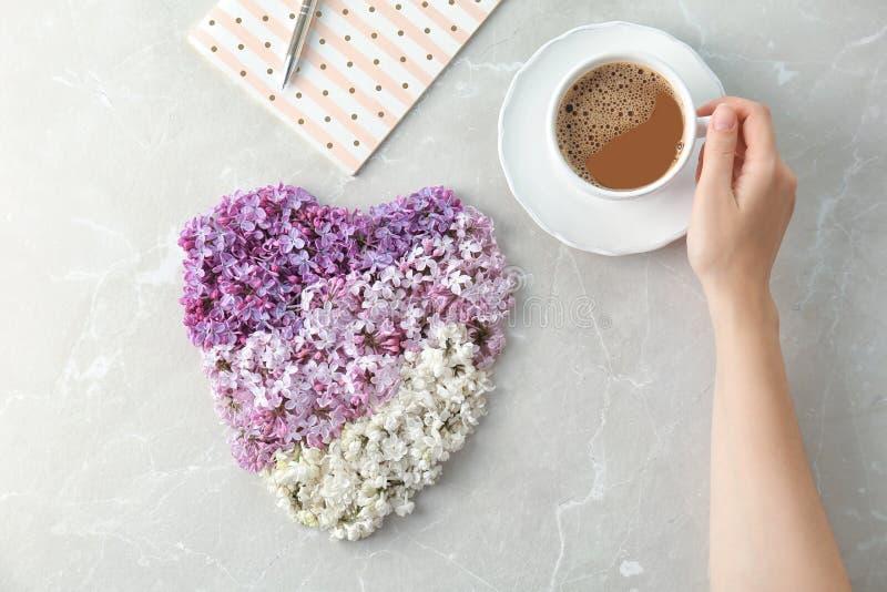 Kvinna med koppen kaffe nära gjord hjärta royaltyfri bild