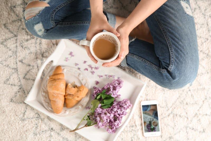 Kvinna med koppen kaffe och magasinet med smakliga giffel och den härliga blomstra lilan på matta royaltyfri bild