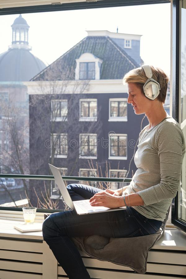 Kvinna med kort hår som sitter nära öppnat fönster på fönsterbrädan med kanalsikt med bärbara datorn och lyssnar till musik i hör arkivfoto