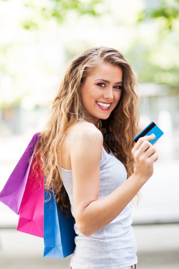 Kvinna med kreditkort- och shoppingpåsar arkivfoto