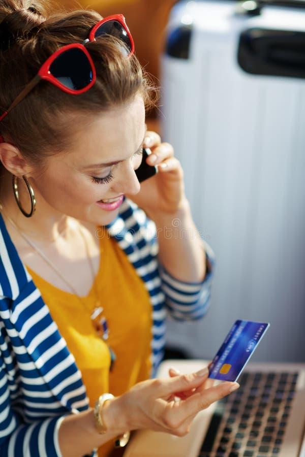 Kvinna med kreditkorten genom att använda mobiltelefonen för att betala för hotellrum royaltyfria foton
