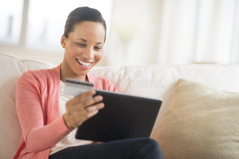 Kvinna med kreditkorten och bärbar dator som direktanslutet hemma shoppar royaltyfri fotografi
