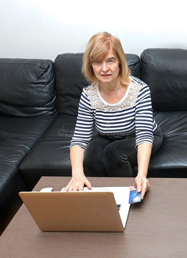 Kvinna med kreditkorten på internet arkivbild