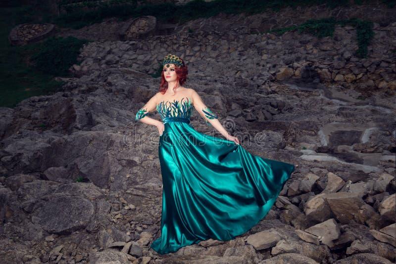 Kvinna med kronan på huvudet i den gröna långa klänningen som poserar att se som sid royaltyfri fotografi