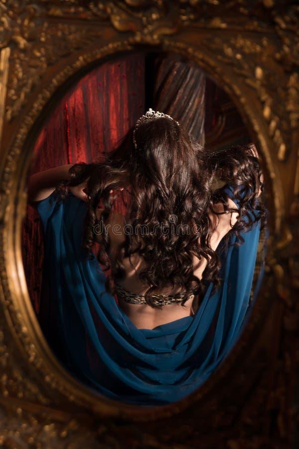 Kvinna med krullat hår reflekterat i spegel antik fåtölj sniden inre lyx royaltyfri fotografi