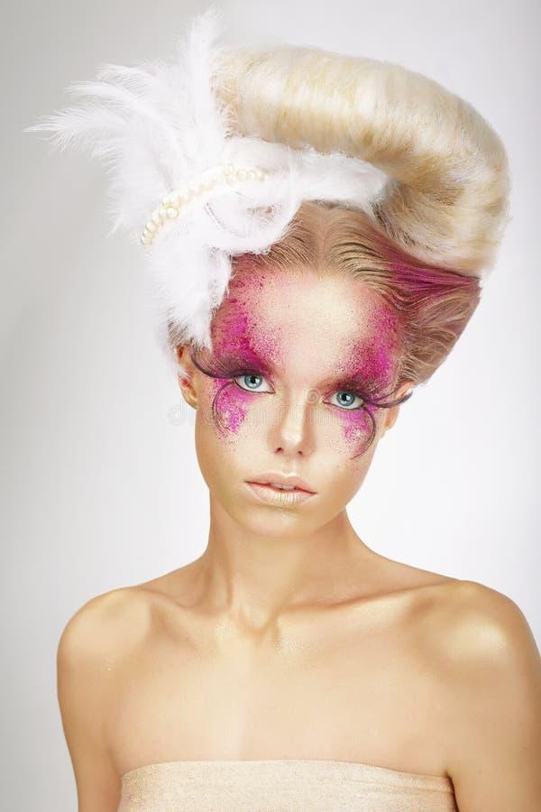 Kvinna med kulöra rosa färger för hud, falska snärtar och den vita fjädern royaltyfria foton