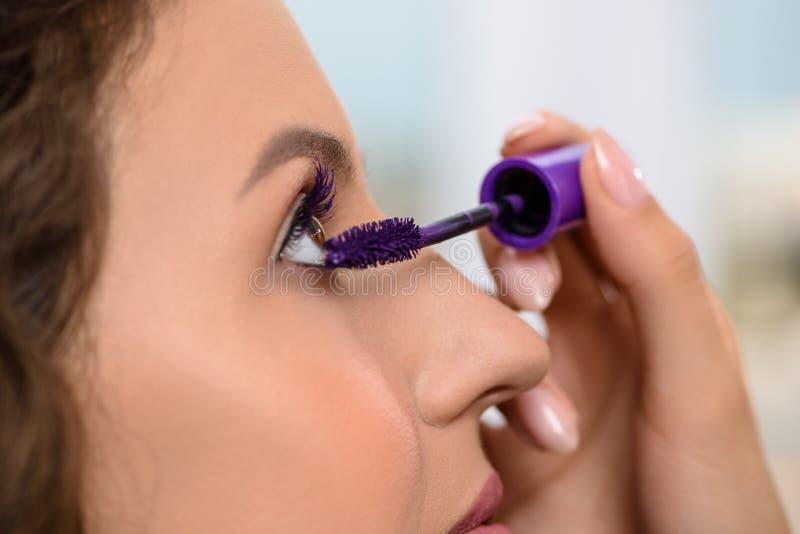 Kvinna med långa ögonfrans under makeup i salong royaltyfri foto