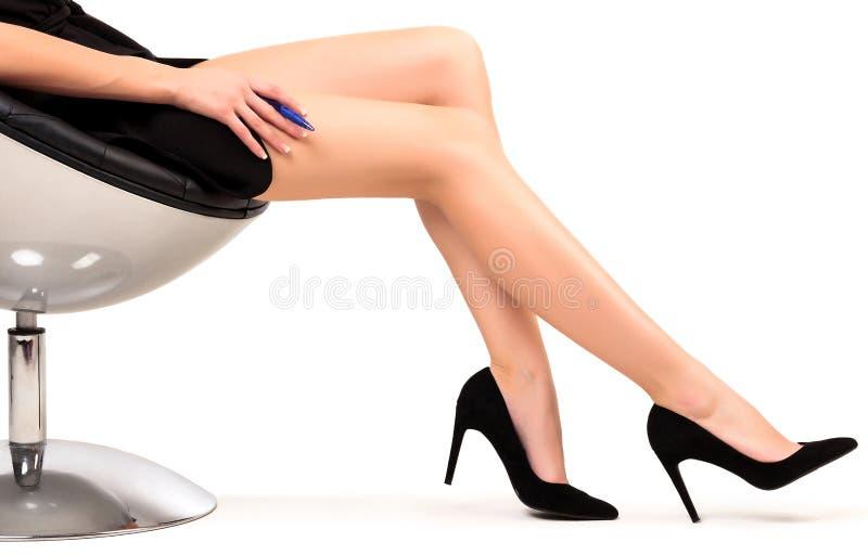 Kvinna med långa ben som sitter i en stol arkivfoton