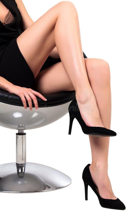 Kvinna med långa ben som sitter i en stol arkivfoto