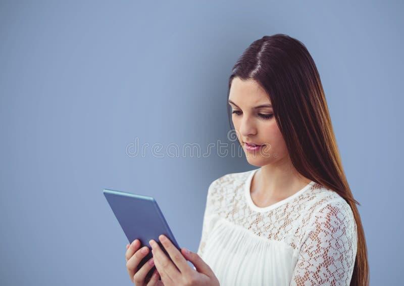 Kvinna med långt brunt hår genom att använda minnestavlaPC över blå bakgrund fotografering för bildbyråer